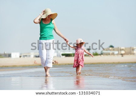 woman mother walking with little child girl on sea ocean beach at vacation - stock photo