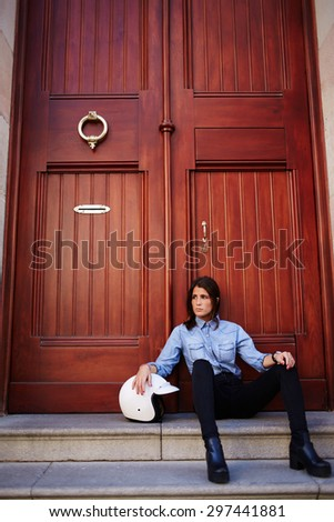 Woman motorcyclist rest after racing while sitting with her motor helmet against wooden door entrance with copy space for your text message,stylish female hipster looking sideways relaxing in the city - stock photo
