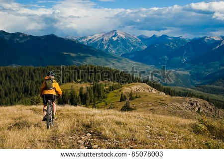 Woman mountain-bike riding on ridge with Ragged Mountains in the distance - stock photo