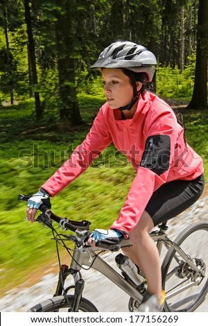 Woman mountain biking in forest motion blur training race - stock photo