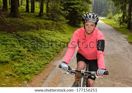 Woman mountain biking through forest road blur motion - stock photo