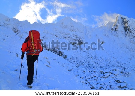 Woman mountaineer ascending on snow covered mountain trail  - stock photo