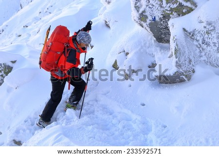 Woman mountaineer ascending on snow covered mountain trail