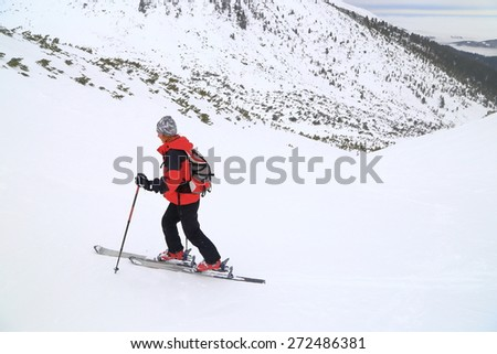 Woman mountaineer ascending on touring skis in overcast winter day - stock photo