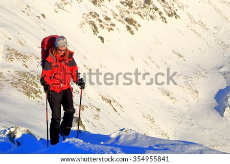 Woman mountaineer carries a backpack on snow covered mountain in winter time, Retezat massif, Romania - stock photo
