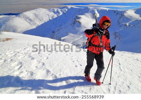 Woman mountaineer carries a pair of skies on off piste route - stock photo