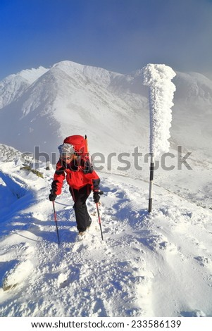Woman mountaineer on snowy trail above the clouds - stock photo