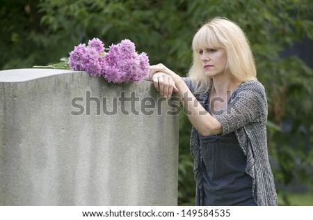 Woman mourns in cemetery resting on gravestone in closeup - stock photo