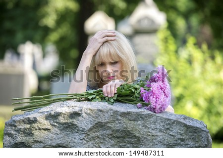 Woman mourns  with her hand on headstone in cemetery in closeup - stock photo