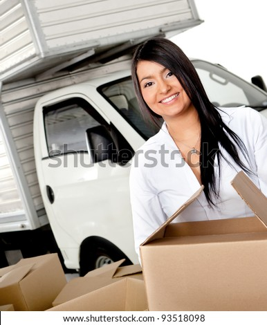 Woman moving house carrying boxes - isolated over a white background - stock photo