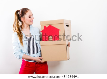 Woman moving into new apartment carrying cartons boxes with red paper house. Young girl arranging interior and unpacking at home.