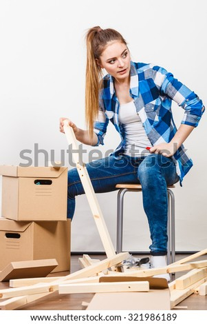Woman moving into new apartment house assembling furniture using screwdriver. Young girl arranging interior and unpacking boxes. DIY.