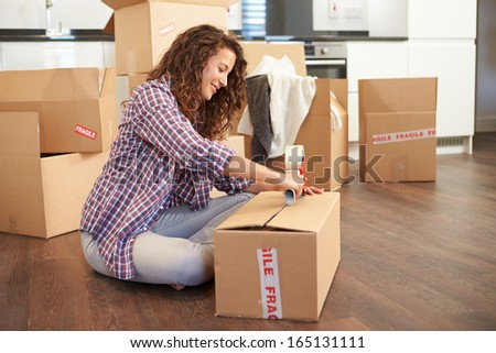 Woman Moving Into New Home And Unpacking Boxes - stock photo