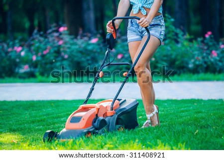 Woman mowing lawn in residential back garden on sunny day. - stock photo