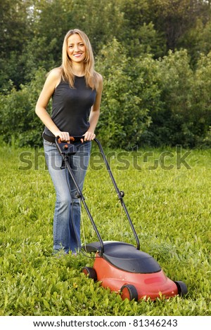 woman mowing with lawn mower - stock photo