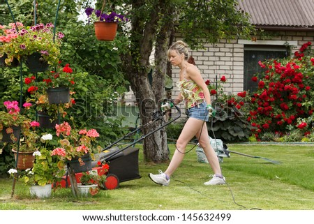 Woman mows the garden with electric mower - stock photo