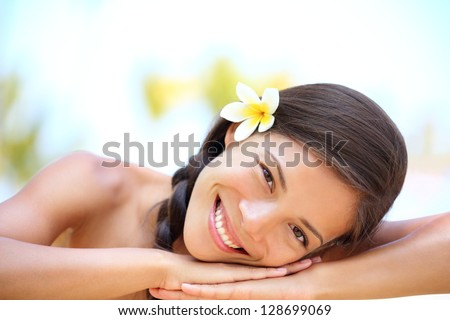 Woman natural beauty. Beautiful smiling girl outdoor portrait at massage spa. Serene happy ethnic woman relaxing looking joyful at camera. Mixed race Asian / Caucasian female model outdoors. - stock photo