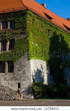 Woman near ancient house in the ivy - stock photo
