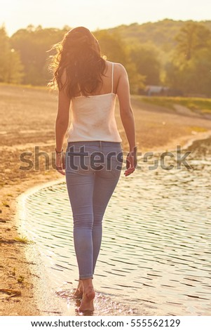 Woman near lake in the evening sunset