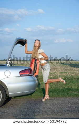 Woman near the car, with her baggage - stock photo