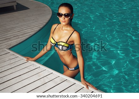 woman near the pool, wearing glasses and swimsuit, tans and relaxing on vacation, healthy athletic body - stock photo