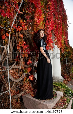woman near the wall of autumn leaves  - stock photo