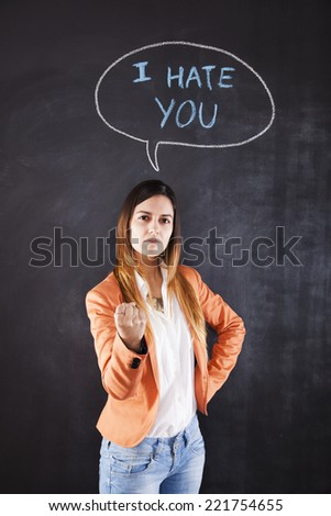 Woman next to a chalkboard with the words I hate you - stock photo
