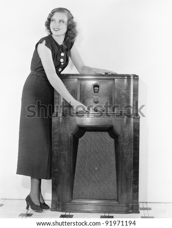Woman next to a radio turning the knobs