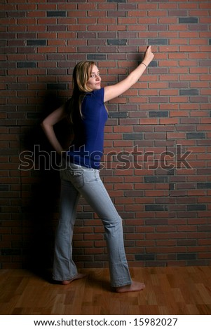 woman next to brick wall pointing to area for user supplied text - stock photo