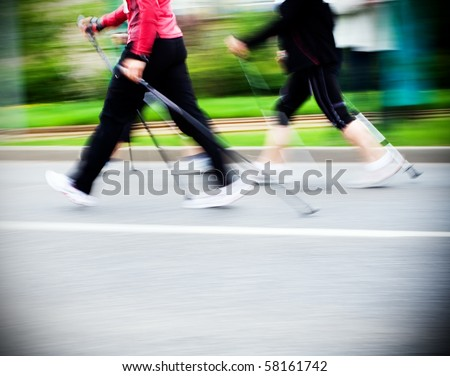 Woman nordic walking race on city streets. Walkers in marathon competition running fast - stock photo