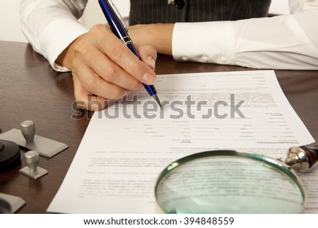 Woman notary, lawyer signs the documents in office - stock photo