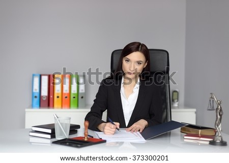 Woman notary public signing the power of attorney or contract.  - stock photo