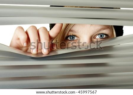 Woman observes a room through a jalousie - stock photo
