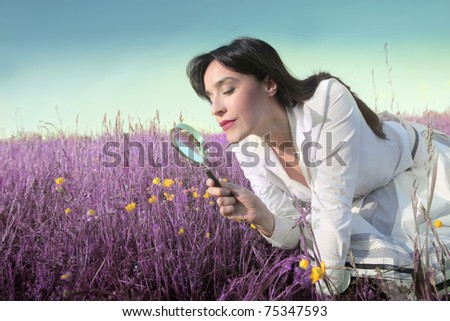 Woman observing some flowers through a magnifying glass - stock photo