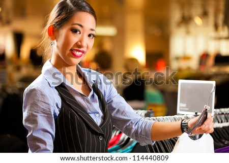 Woman of Asian - Chinese - origin in a shopping mall downtown looking for clothes