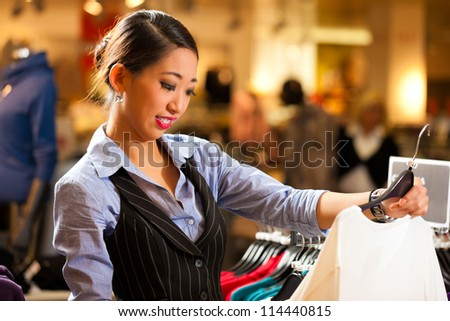 Woman of Asian - Chinese - origin in a shopping mall downtown looking for clothes - stock photo