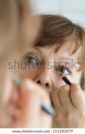 Woman of middle age in the bathroom mirror at the make-up  - stock photo