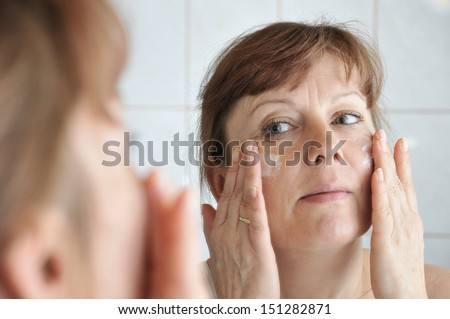 Woman of middle age in the bathroom mirror at the make-up