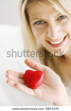 woman offering her heart - stock photo