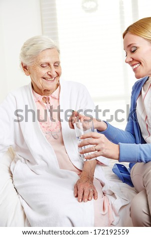 Woman offering pill to sick senior citizen at home - stock photo