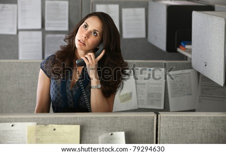 Woman office worker rolls eyes while on telephone - stock photo