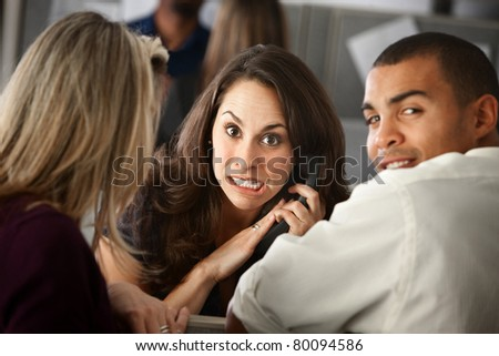 Woman office worker silences her colleague while on a phone call - stock photo