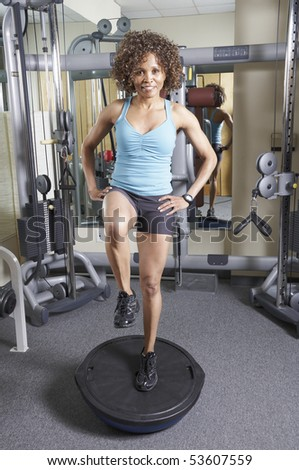 Woman on a balance trainer exercising in the gym - stock photo