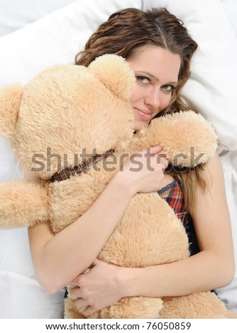 woman on a bed in an embrace with teddybear. Isolated on white background - stock photo