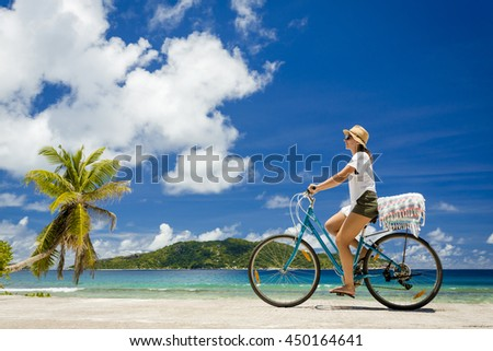 Woman on a bicycle ride along The Beach at Seychelles