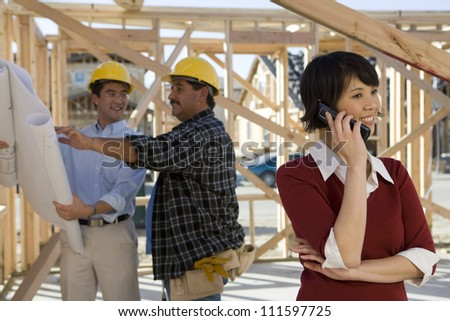 Woman on a call with contractors discussing in background at construction site - stock photo