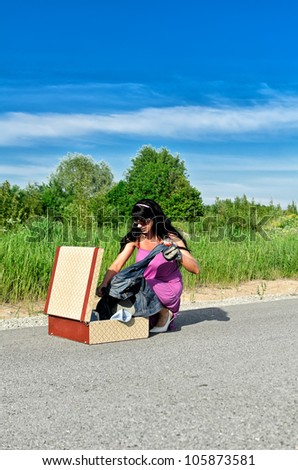 Woman on a road getting clothes from suitcase. - stock photo