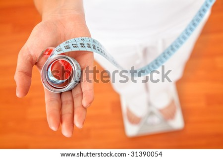 Woman on a scale with a measuring tape - stock photo