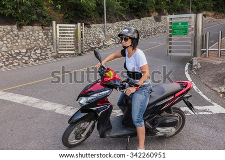 Woman on a scooter with helmet and sunglasses - stock photo