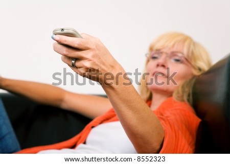 Woman on a sofa with a tv remote control (focus on remote control) - stock photo